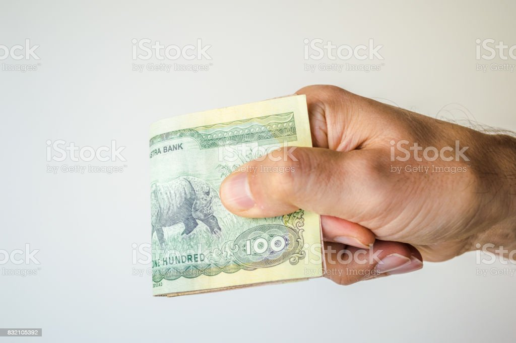 Man holding Nepal Rupees notes in his hand stock photo