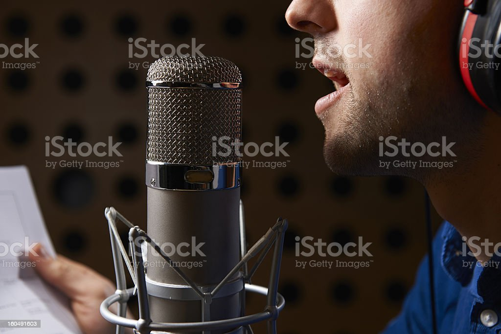 Man Holding Notes And Talking Into Studio Microphone stock photo