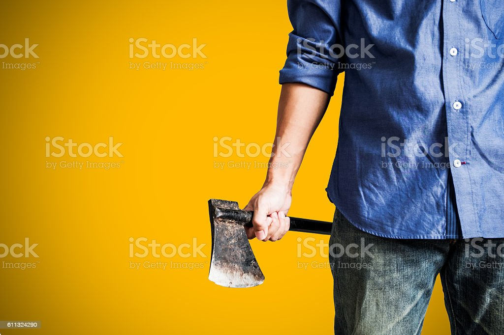 Man holding old rusty axe, on yellow background stock photo