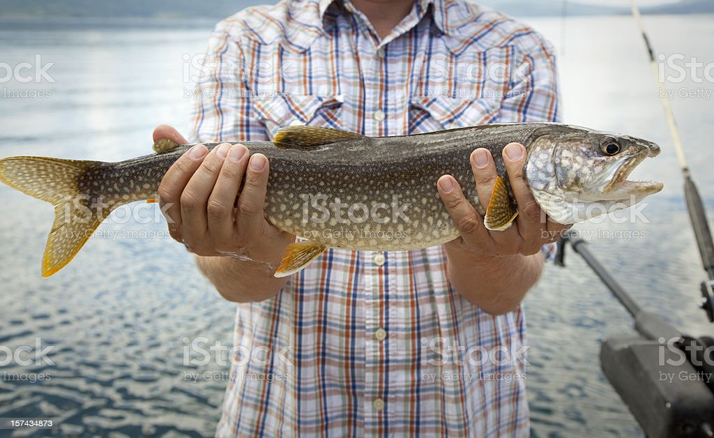 A man holding out a trout that he caught stock photo