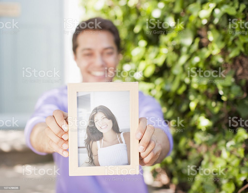 Man holding out photograph of girlfriend royalty-free stock photo