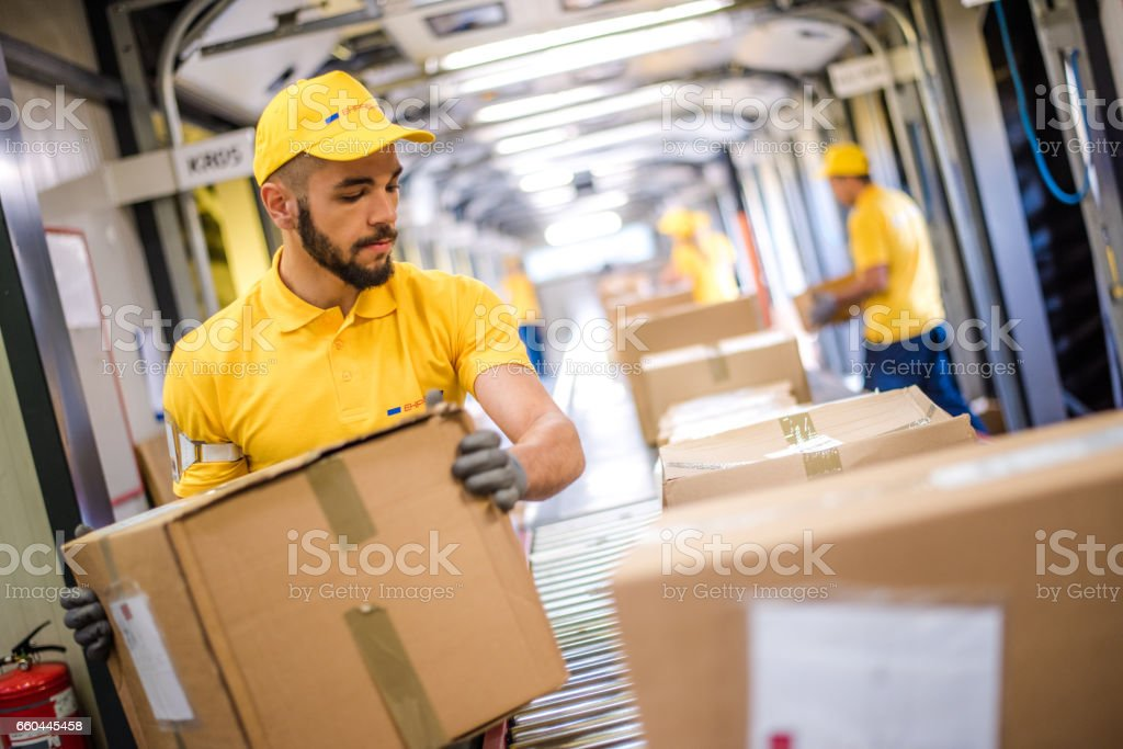 Male worker picking up packed box from conveyer belt in warehouse.