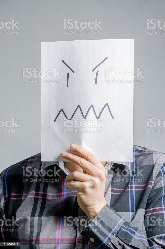 Man holding paper with angry face in front of head stock photo