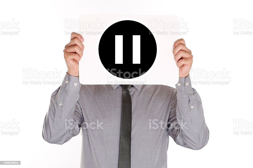 Man Holding Paper With Pause Button In Front Of Head stock photo