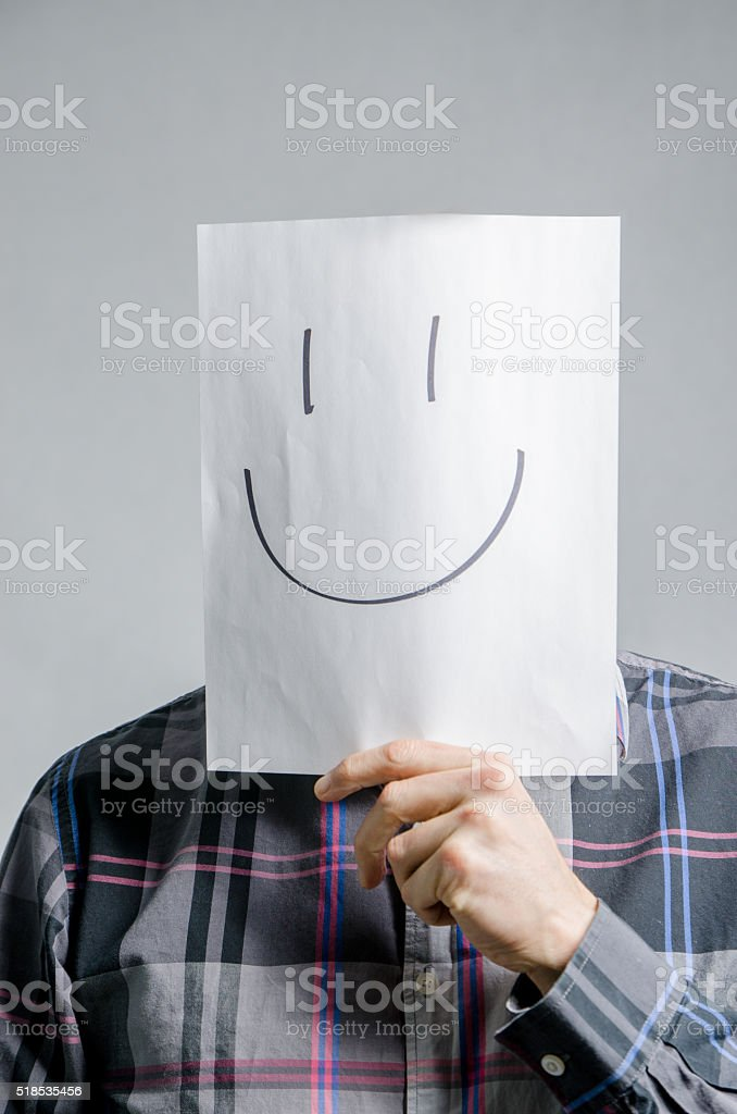 Man holding paper with smiley face in front of head stock photo