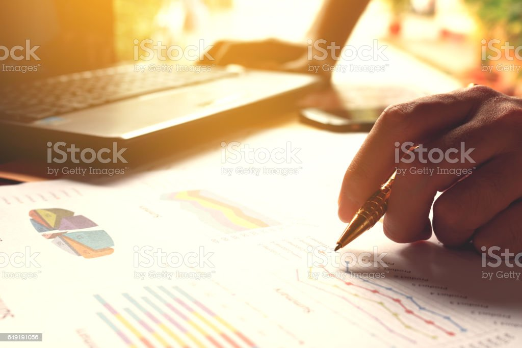 Man holding pen and thinking calculate cost and expenses and using...