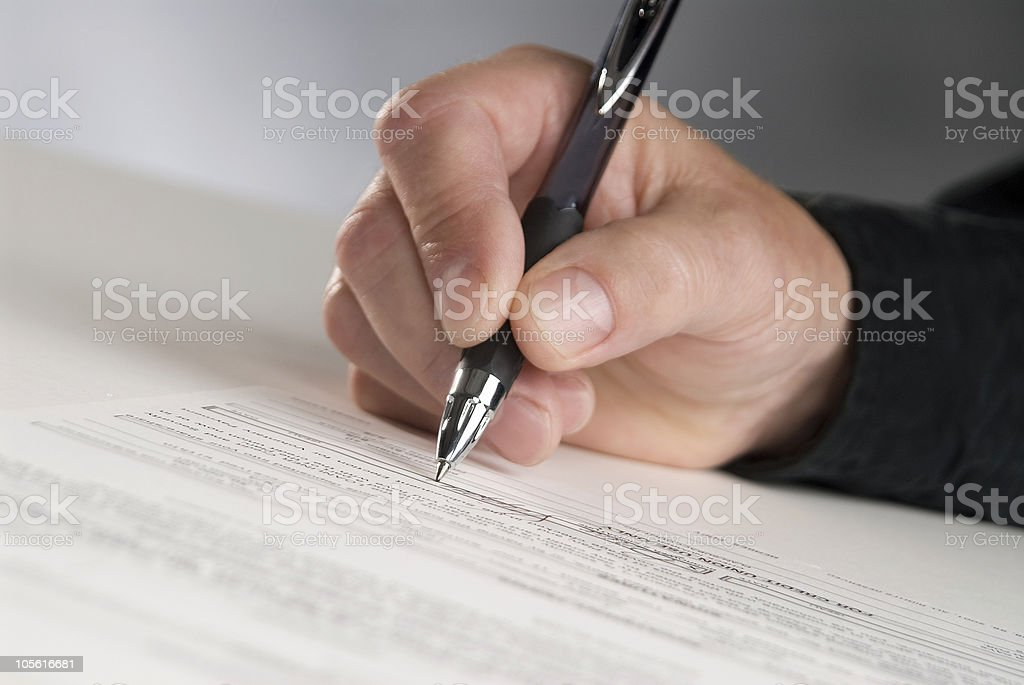 Man holding pen signing document stock photo