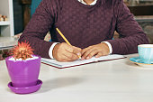 Man holding pencil and writing on a paper in the