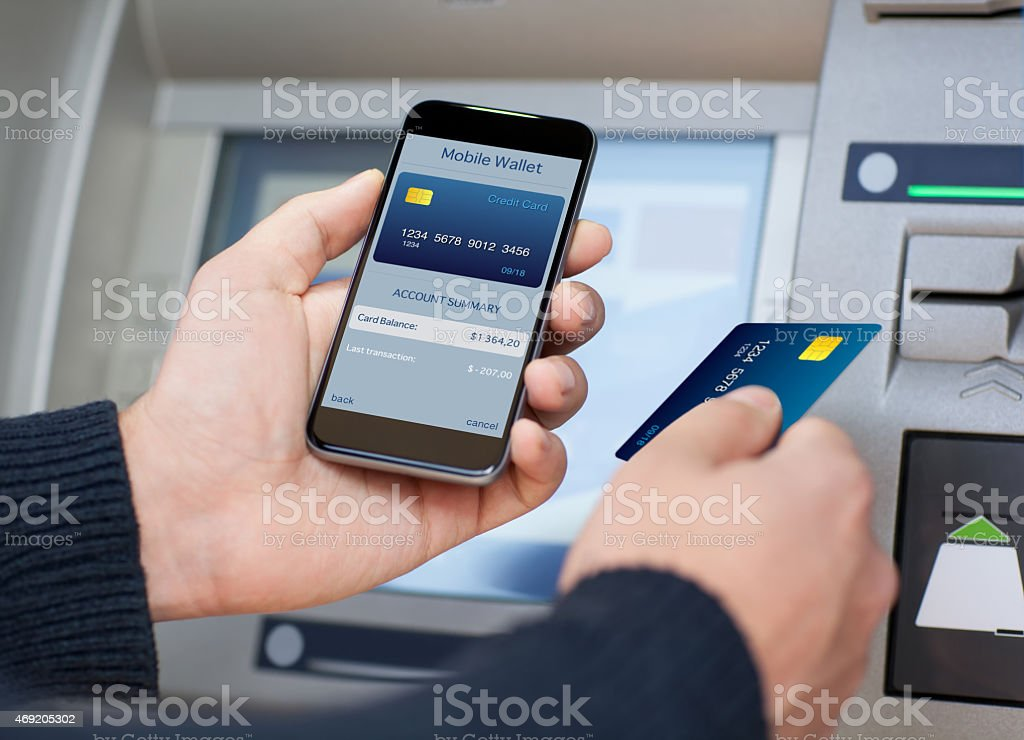 man holding phone with mobile wallet at the ATM stock photo