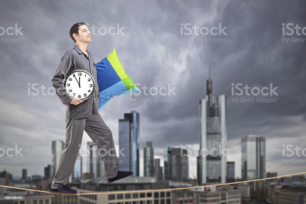 Man holding pillow and clock sleepwalking on a rope stock photo