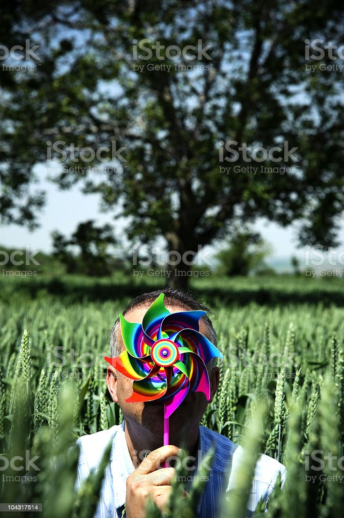 man holding pinwheel him face in nature stock photo