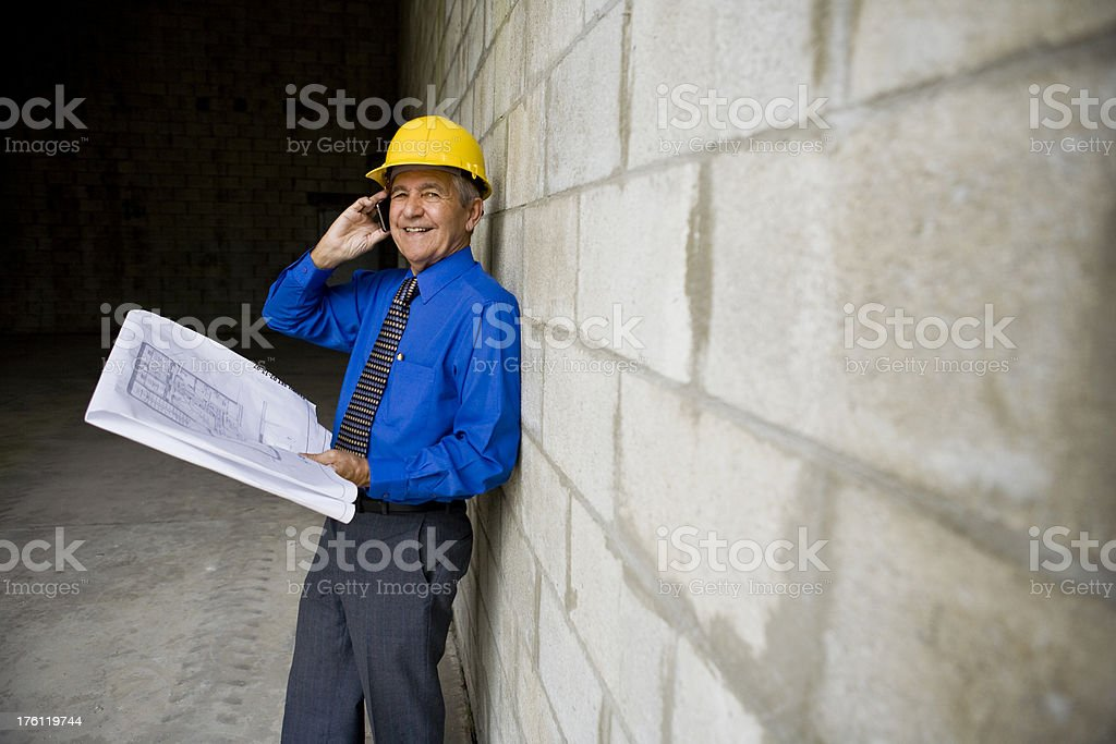 Man holding plans at construction site royalty-free stock photo