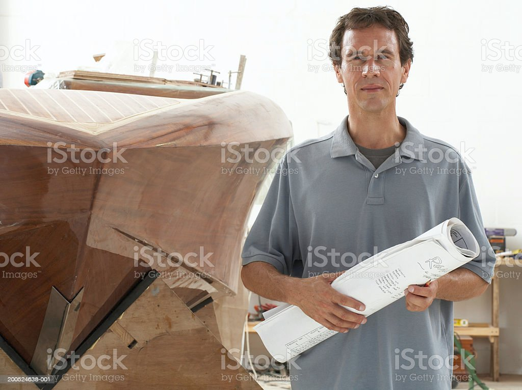Man holding plans in boat building workshop, portrait royalty-free stock photo