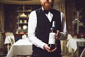 Man holding polished bottle with alcohol