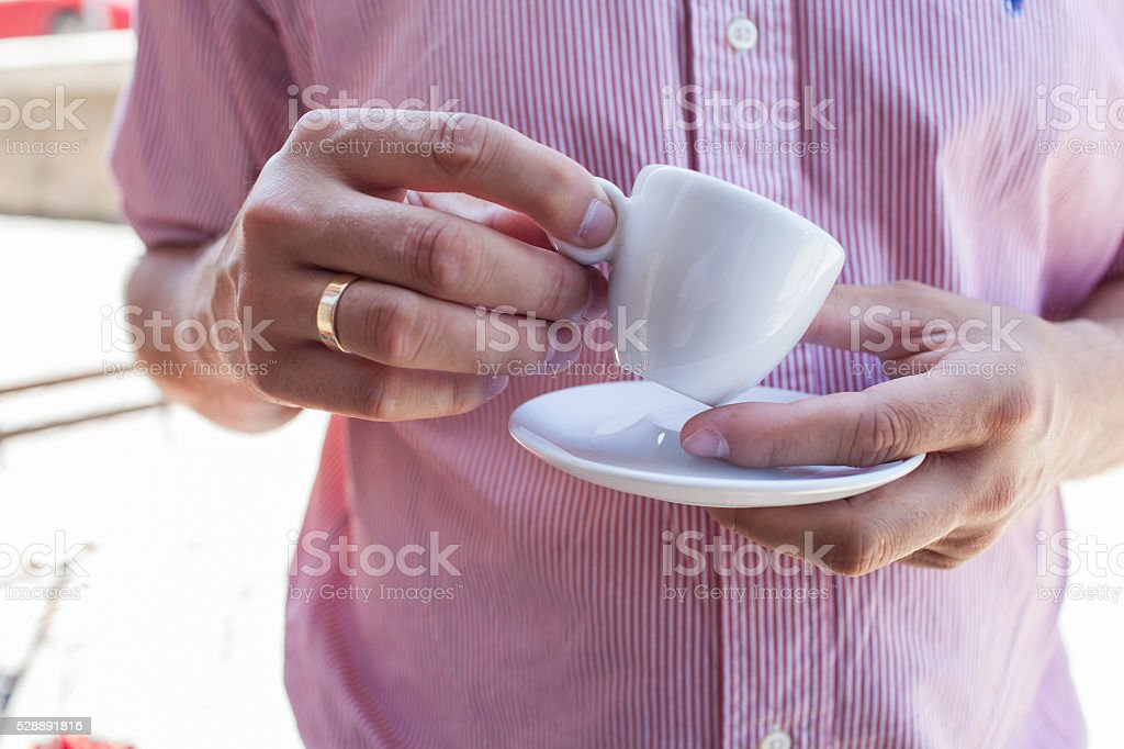 Man holding porcelain cup with his morning espresso. Close up stock photo