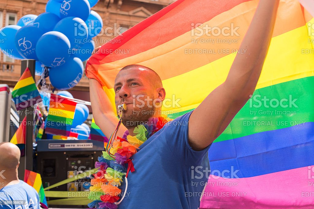 Man holding rainbow flag taking part in London's Gay Pride stock photo