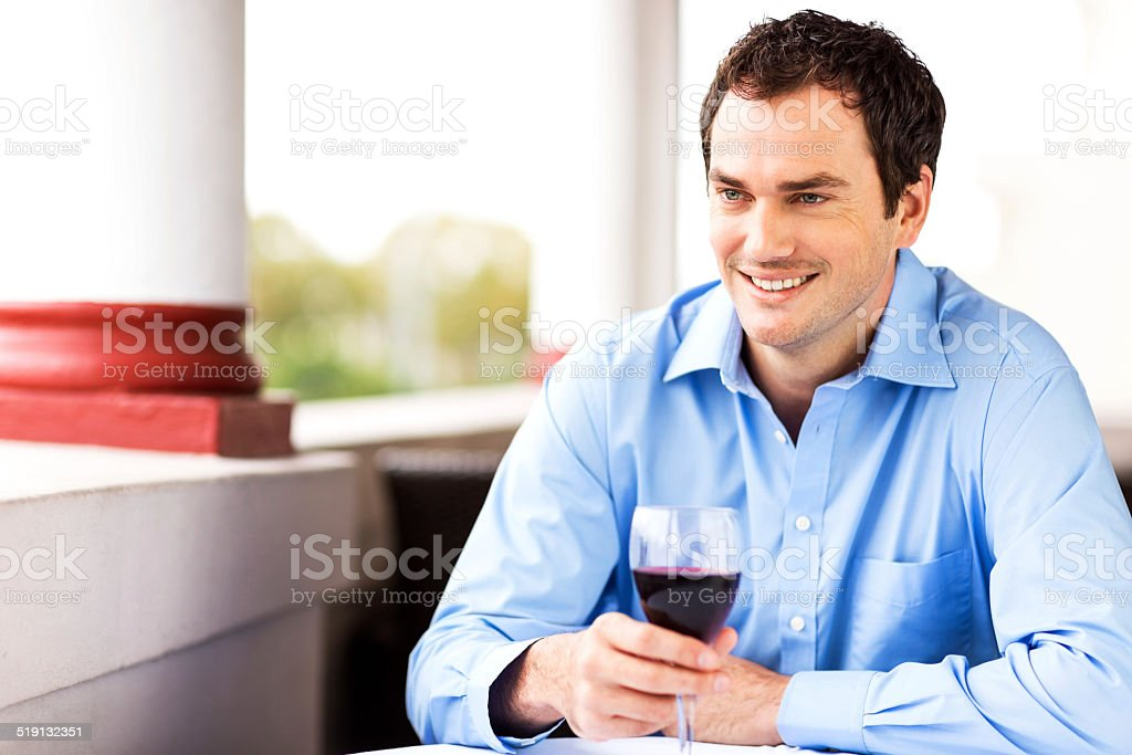Man Holding Red Wine Glass While Looking Away At Restaurant stock photo