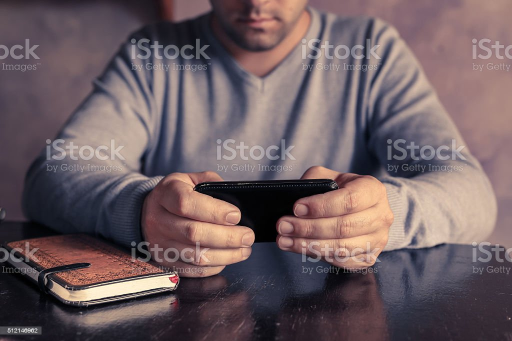 Man holding smartphone with notebook stock photo