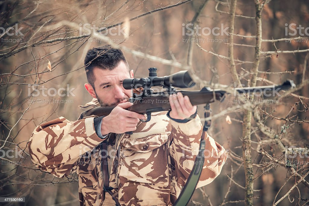 Man holding sniper and shooting on an open season stock photo
