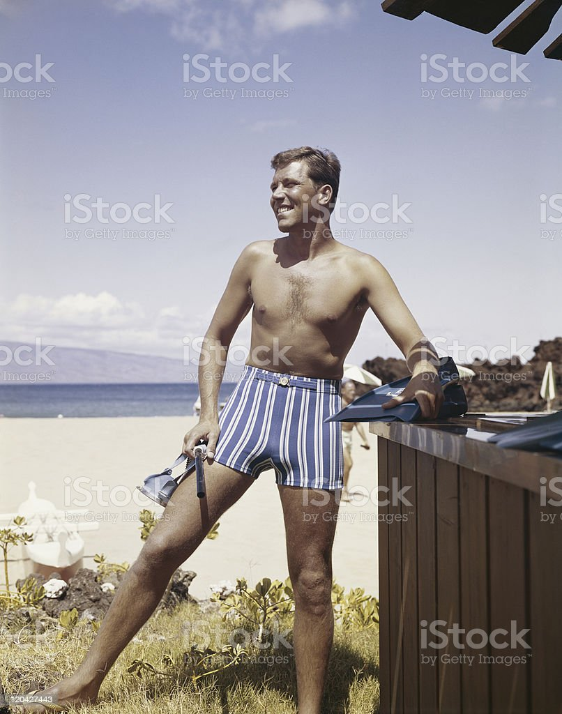 Man holding snorkel and flippers on beach, smiling royalty-free stock photo