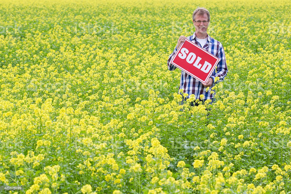 Man Holding Sold Sign In Field royalty-free stock photo
