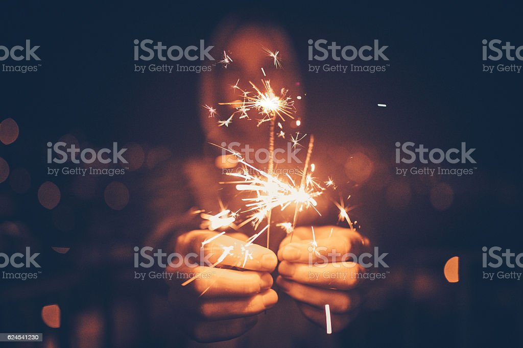 Man holding sparklers in his hands stock photo