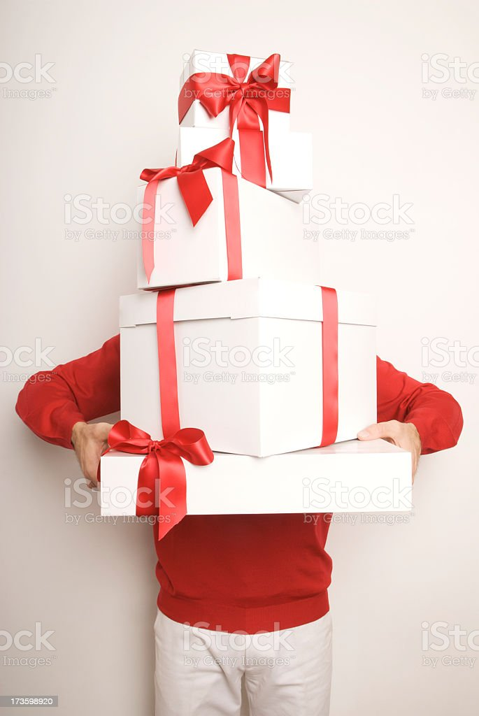 Man Holding Stack of Christmas Holiday Presents with Red Bows stock photo
