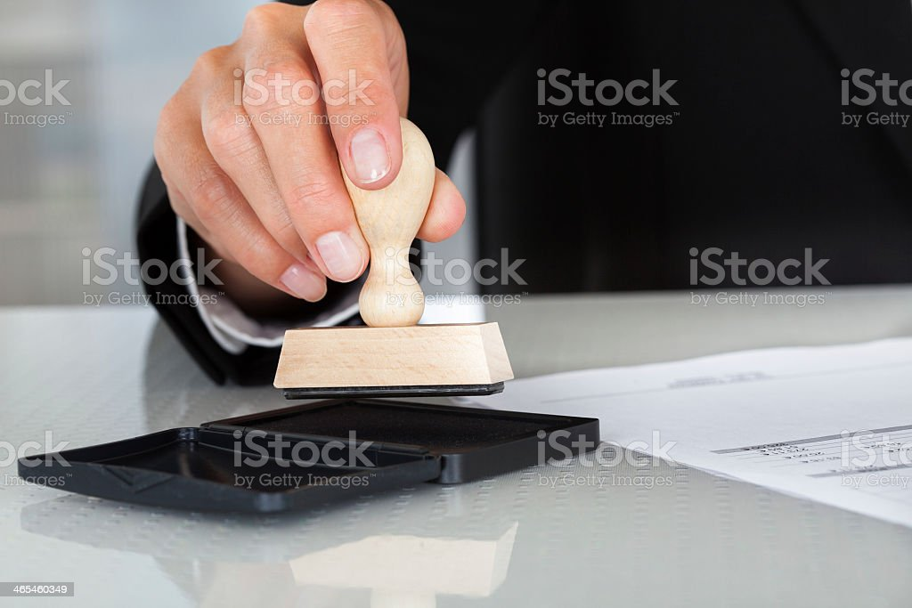 Man holding stamp over ink pad to stamp a piece of paper stock photo