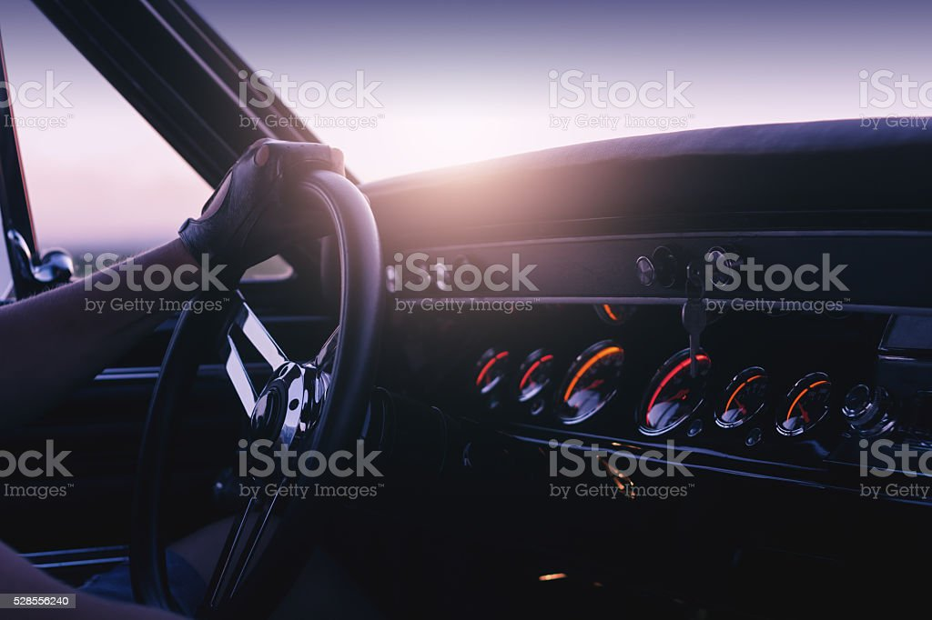 Man holding steering wheel inside car at sunset stock photo