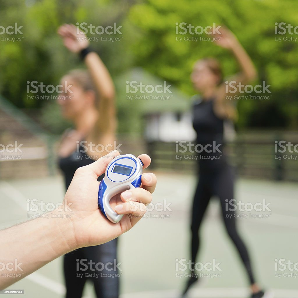 Man holding stopwatch in front of female exercise class stock photo