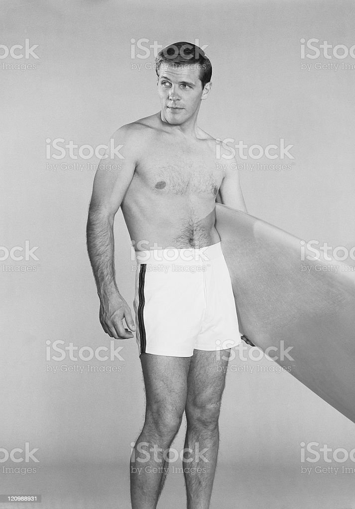 Man holding surfboard against white background stock photo
