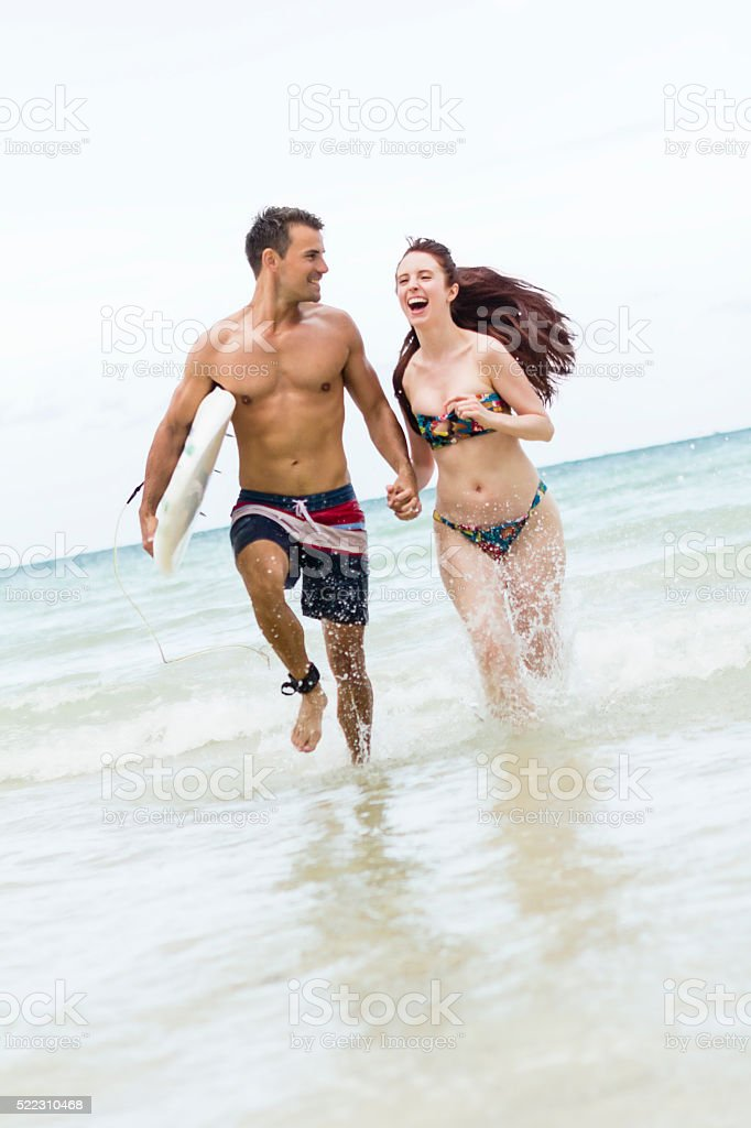 Man holding surfboard, hand of pretty girl running in waters stock photo
