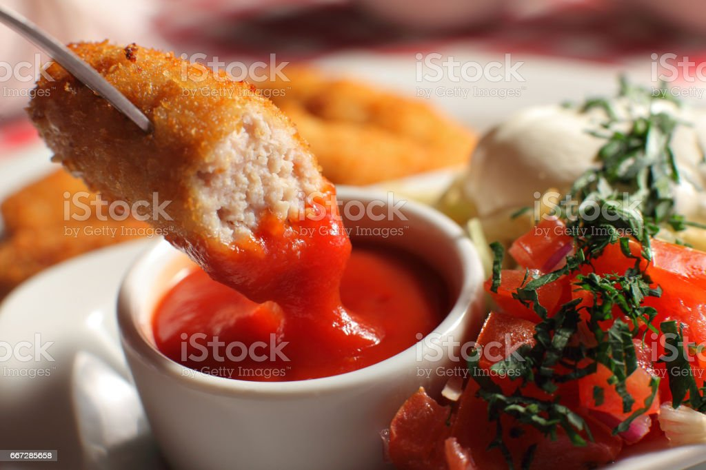 man holding tasty nugget and bowl with sauce on table, closeup stock photo