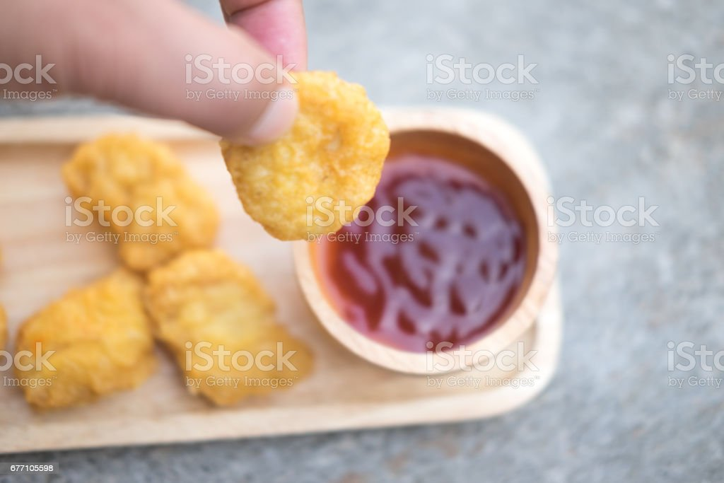 Man holding tasty nugget and bowl with sauce on table, selective focus stock photo