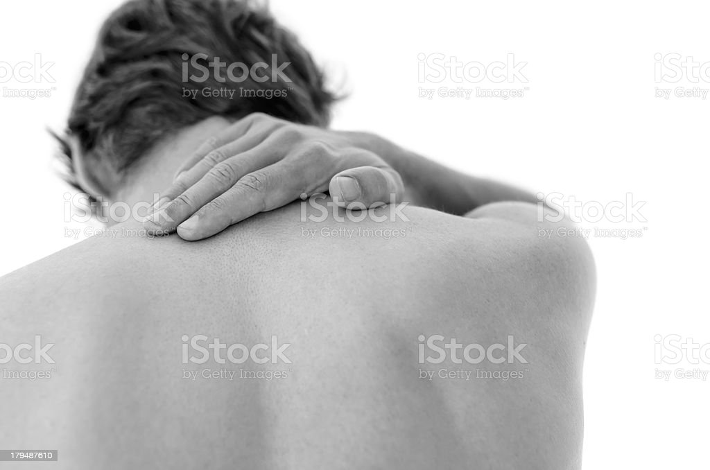 A man holding the back of his neck in pain stock photo