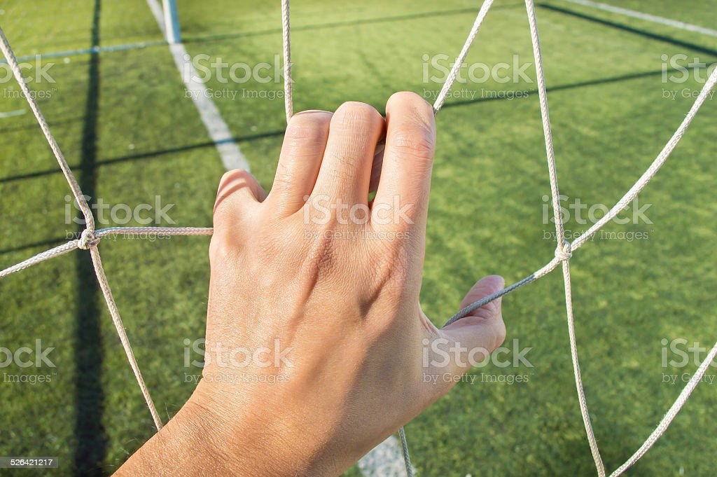 man holding the net of the football goal stock photo