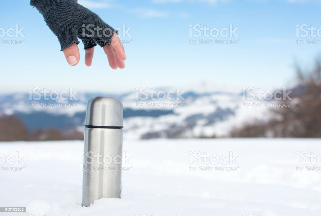 Man holding thermos in on a snowy mountain stock photo