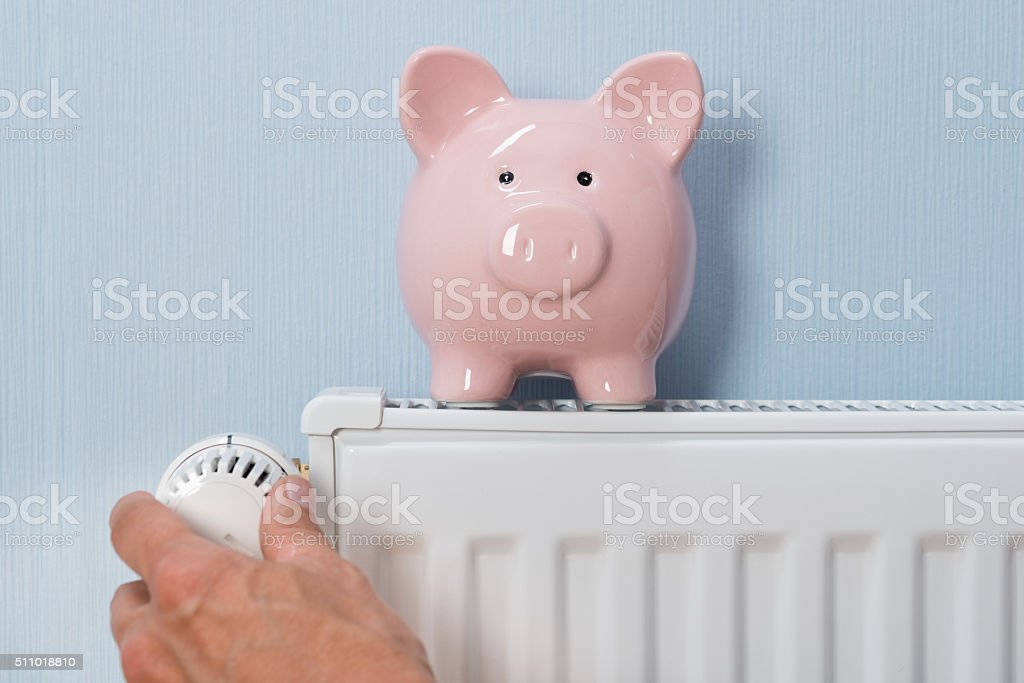 Man Holding Thermostat With Piggy Bank On Radiator stock photo