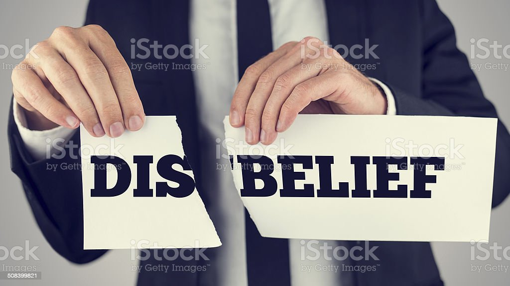 Man holding torn paper with the words Dis-Belief stock photo