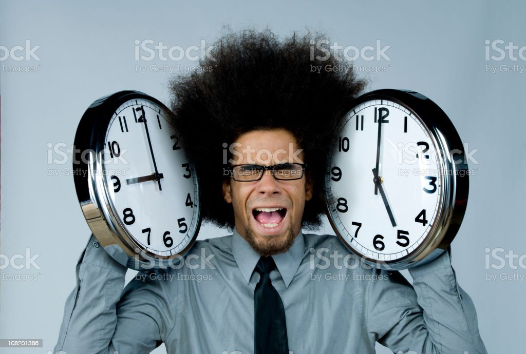 Man Holding Two Clocks Up to Ears stock photo