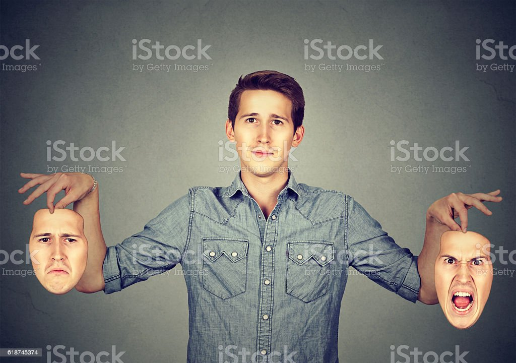 Man holding two different emotion masks stock photo