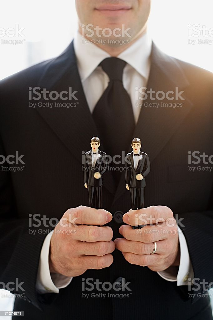 Man holding two groom wedding cake figurines royalty-free stock photo