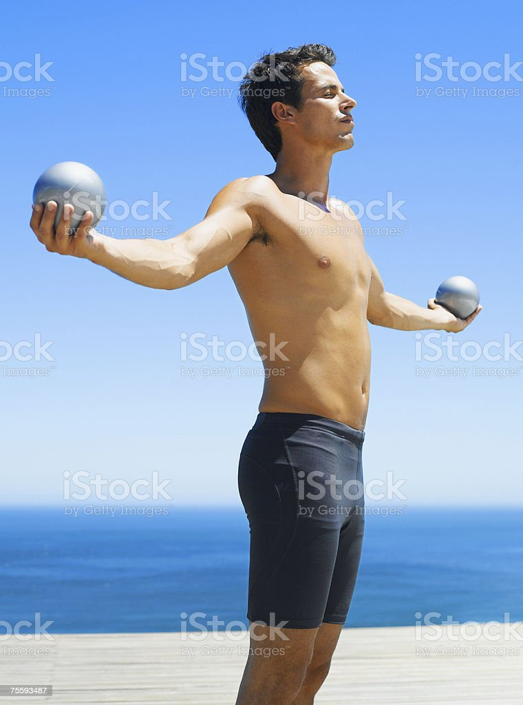 Man holding two small exercise balls with outstretched arms royalty-free stock photo