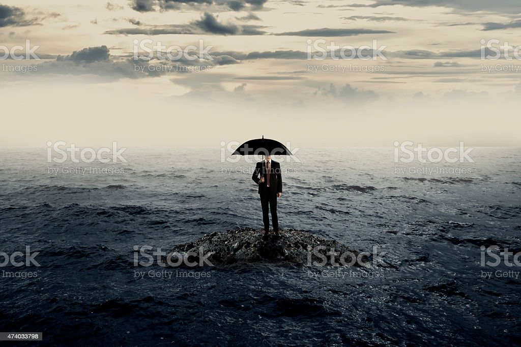 Man Holding Umbrella Stading On The Rock On The Sea stock photo