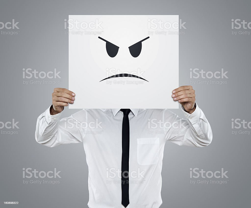 A man holding up a card with an angry face stock photo