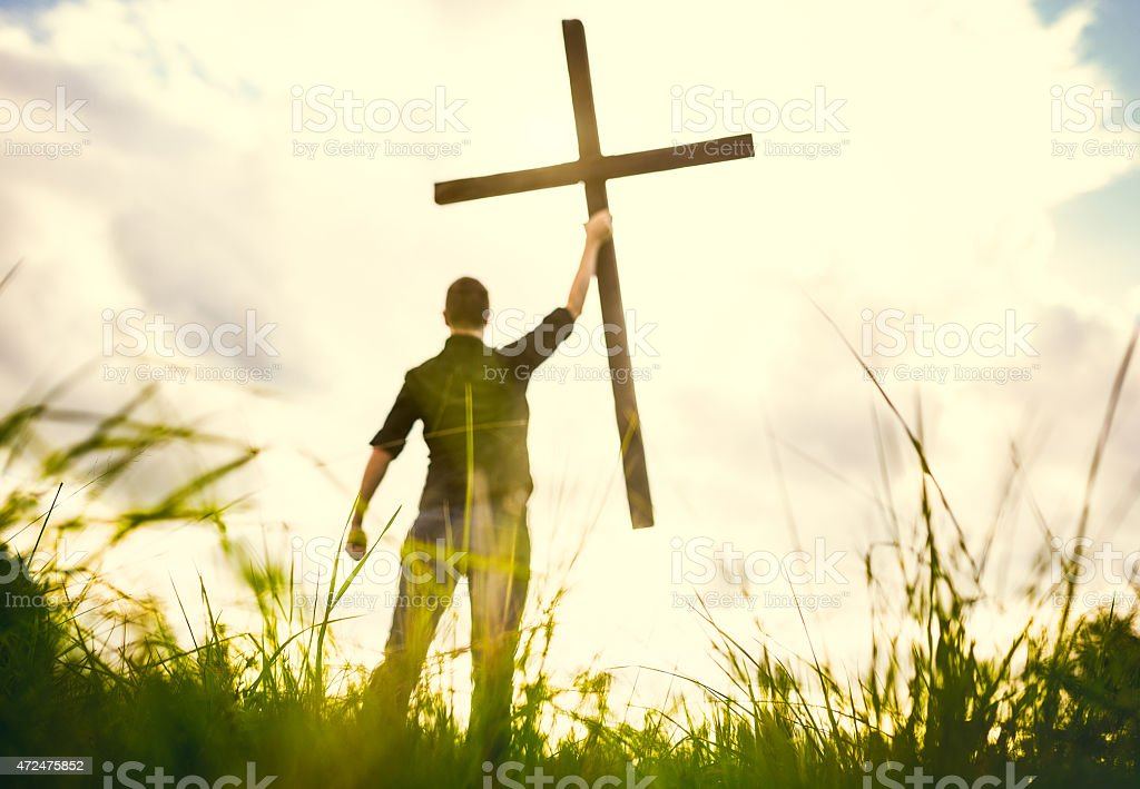 Man Holding Up Cross of Christ stock photo