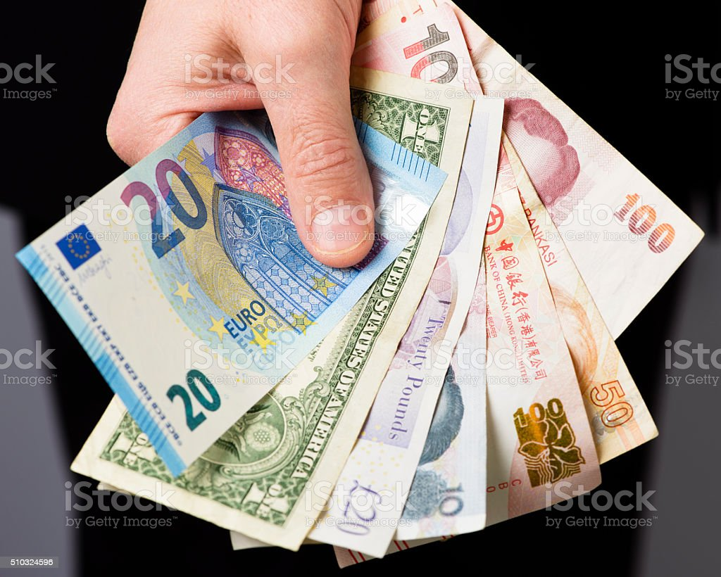 Man Holding Various International Currency Bank Notes stock photo