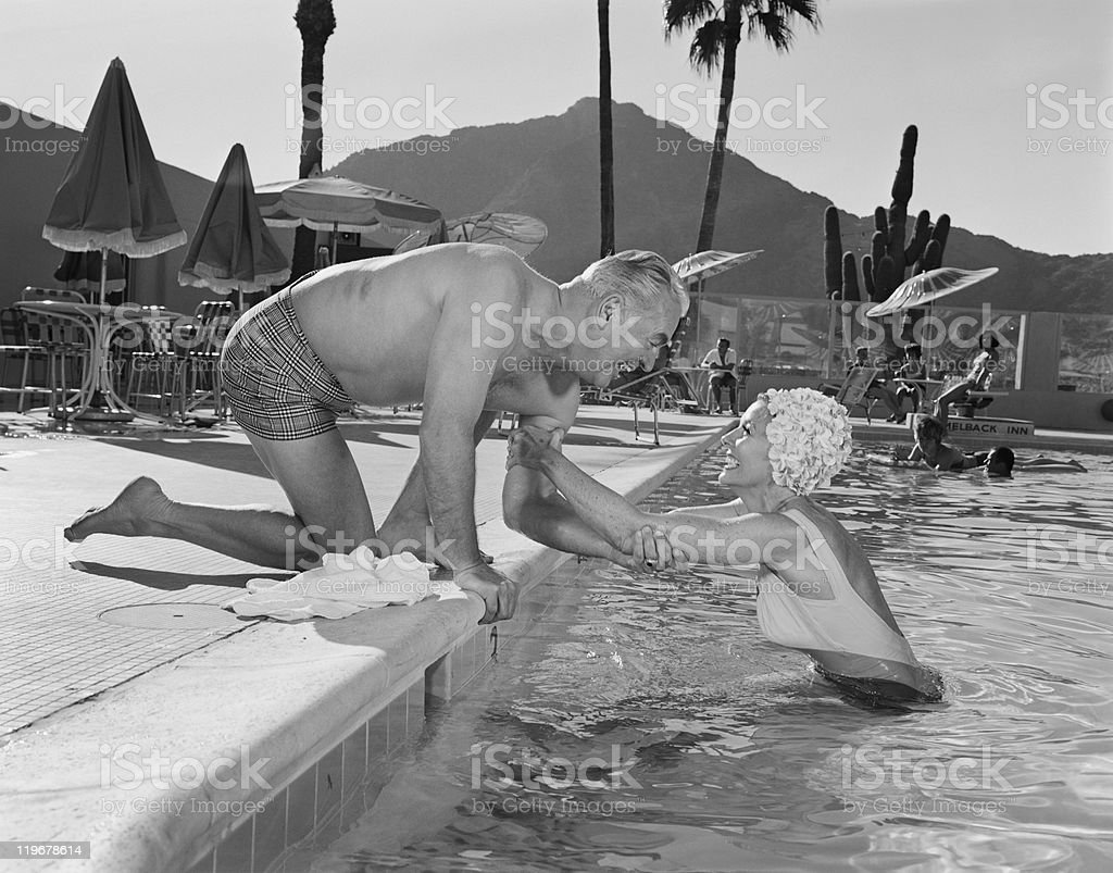 Man holding woman's hand at swimming pool, smiling stock photo