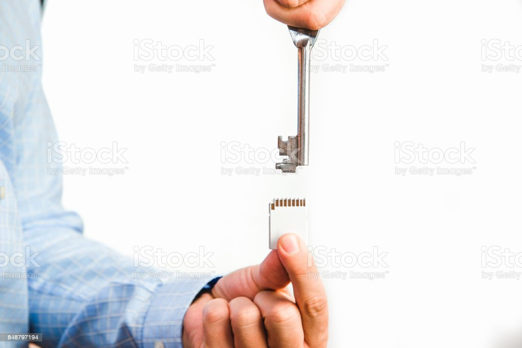 Man holds a key in his hand and tries to open memory card. stock photo