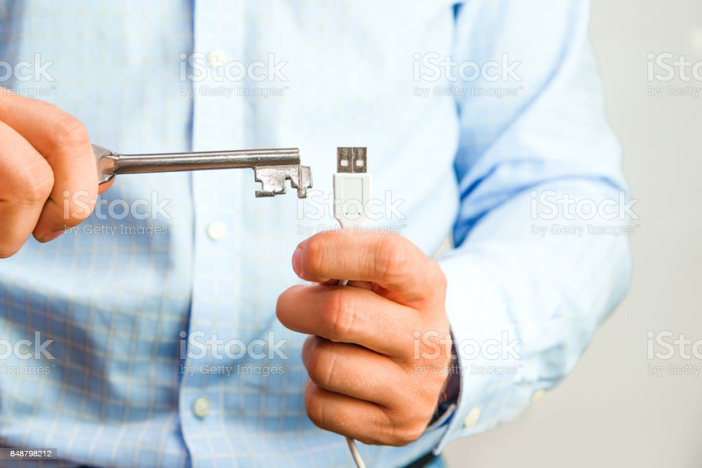 Man holds a key in his hand and tries to open USB. stock photo